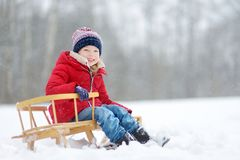 Funny little girl having fun with a sleigh in beautiful winter park. Cute child playing in a snow. stock photos