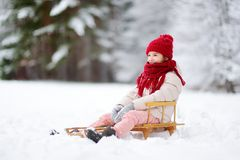 Funny little girl having fun with a sleight in beautiful winter park Royalty Free Stock Images