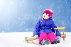 Funny little girl having fun with a sleight in beautiful winter park stock photo