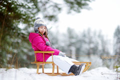 Funny little girl having fun with a sleight in winter park Stock Images