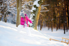 Funny little girl having fun with a sleight in winter park Royalty Free Stock Image