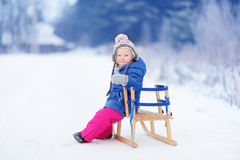 Funny little girl having fun with a sleight in winter park Stock Photos