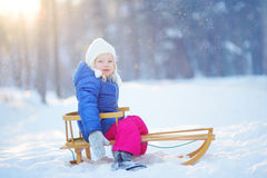 Funny little girl having fun with a sleight in winter park Royalty Free Stock Photography
