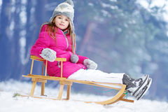 Funny little girl having fun with a sleight in winter park Stock Image