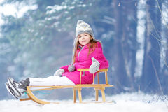 Funny little girl having fun with a sleight in winter park Stock Photo