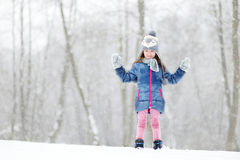 Funny little girl having fun in winter park Stock Photo