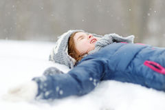 Funny little girl having fun in winter park. Funny little girl having fun in beautiful winter park during snowfall Royalty Free Stock Photo