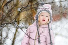 Funny little girl having fun in winter park Stock Images