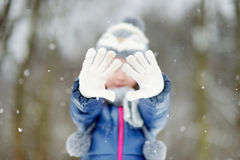 Funny little girl having fun in winter park Royalty Free Stock Images