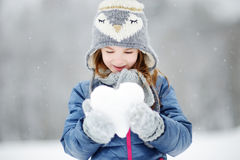 Funny little girl having fun in winter park. Funny little girl holding snow heart in beautiful winter park during snowfall Royalty Free Stock Image