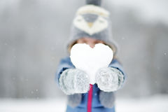 Funny little girl having fun in winter park. Funny little girl holding snow heart in beautiful winter park during snowfall Royalty Free Stock Images