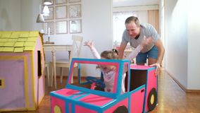 Funny little girl and her father are driving handmade cardboard car. Father and daughter are having fun in living room together stock video footage