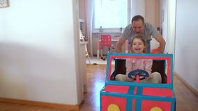 Funny little girl and her father are driving handmade cardboard car. Father and daughter playing in living room together stock video footage
