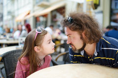 Funny little girl and her father having fun in an outdoor cafe Royalty Free Stock Images