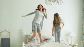 Funny little girl with her loving mother have fun learning dance modern style together watching dancing show on TV and