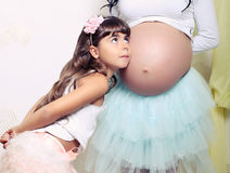Funny little girl with her pregnant mother Royalty Free Stock Photos