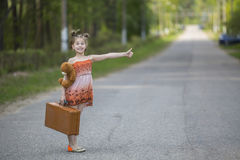 Funny little girl hitchhiker with a suitcase and a teddy bear. Travel. Royalty Free Stock Images