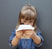 Funny little girl holding a chocolate. Grey background Stock Photos