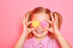 Funny little girl holding colorful macaroons and closing her eyes on pink background. Royalty Free Stock Images