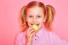 Funny little girl holding and eating colorful macaroon Royalty Free Stock Image