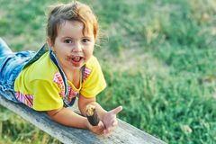 Funny little girl with ice cream. The girl was stained with a sweet dessert Royalty Free Stock Image