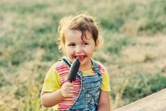 Funny little girl with ice cream. The girl was stained with a sweet dessert Stock Image