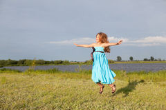 Funny little girl jumping on green field, summer Royalty Free Stock Images