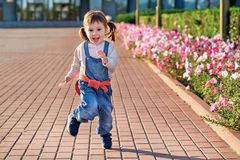 Funny little girl jumping for joy.little girl in denim jumpsuit. Funny girl jumping for joy.Fun little girl running in denim overalls. Cute beautiful child eats Royalty Free Stock Photography