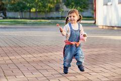 Funny little girl jumping for joy.a young child in denim overalls. Funny girl jumping for joy.Fun little girl running in denim overalls. Cute beautiful child Royalty Free Stock Image