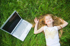 Funny little girl with laptop. In green grass Stock Photos
