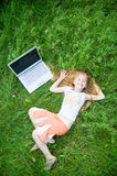 Funny little girl with laptop outside. Funny little girl with laptop in green grass Royalty Free Stock Photos