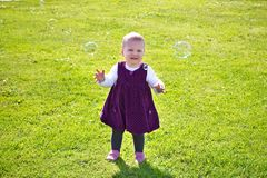 Funny little girl on the lawn Stock Photography