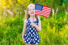 Funny little girl with long blond hair holding an american flag. Funny little girl with long curly blond hair holding an american flag, waving it and laughing on royalty free stock photography
