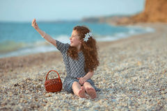 Funny little girl with long curly hair resting on the beach. out Royalty Free Stock Photo