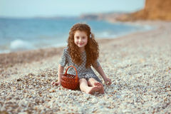 Funny little girl with long curly hair resting on the beach. out Stock Photo