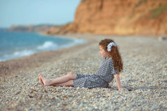 Funny little girl with long curly hair resting on the beach. out Stock Photos