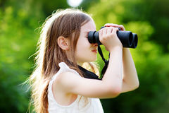 Funny little girl looking through binoculars Royalty Free Stock Images