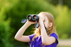 Funny little girl looking through binoculars on sunny summer day Royalty Free Stock Photo