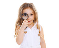 Funny little girl looking through a magnifying glass Royalty Free Stock Photography
