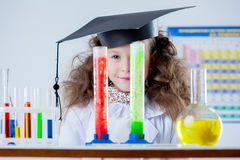 Funny little girl looks out of colorful flasks. Close-up stock image