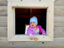 Baby playing in a wooden house royalty free stock image