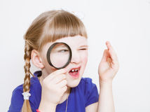 Funny little girl with loupe Stock Photography