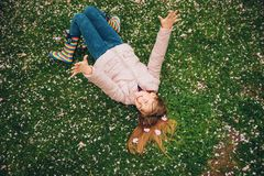 Funny little girl lying on bright green grass, playing with soft flower petals in spring park. Wearing jacket and rain boots, seasonal fashion for kids Royalty Free Stock Image