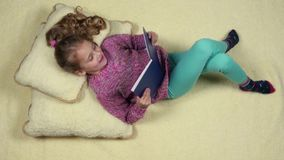 Funny little girl lying on the couch reading a book. Top view.  stock video