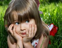 Funny little girl lying in green grass Royalty Free Stock Photography
