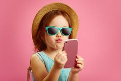 Funny little girl makes a selfie portrait on phone, pulls her lips to the camera, wears a straw hat and sunglasses stock image