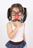 Funny little girl making faces with mustache props Royalty Free Stock Photo
