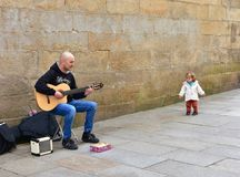 Funny little girl and man playing guitar in a street close to Cathedral. Santiago de Compostela, Spain, 22 Feb 2019. stock photography