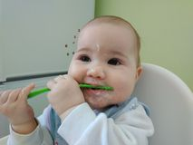 Funny baby eating a large spoon of porridge stock images