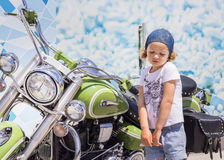 Funny little girl near motorcycles. Royalty Free Stock Photography